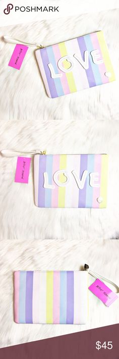 "Betsey Johnson Love Wristlet This is an adorable Wristlet by Betsey Johnson.  It's striped in pastel colors with ""Love"" stitched on the front.  It's a larger Wristlet measuring 11"" x 7 3/4"".  Material of shell is 100% polyurethane and lining is 100% polyester.  No trades. Betsey Johnson Bags Clutches & Wristlets"