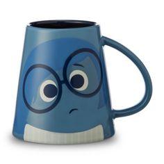 """Concediti il piacere di una bevanda calda servita in questa tazza ispirata al film Inside Out. La tazza dalla forma esclusiva è decorata con immagini vivaci di Tristezza su un lato e la scritta """"One of those days"""" sull'altro."""