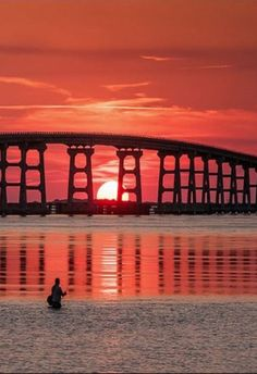 """A fisherman completes his cast into a strip of smooth """"red water"""" as the sun settles behind the Bonner Bridge at Oregon Inlet in Outer Banks, North Carolina at the Cape Hatteras National Seashore"""
