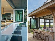 Cozinha com janela ampla que abre para espaço externo, onde há balcão e cadeiras altas como as de bar.