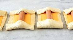 Rectangles of crescent dough, each topped with a slice cheese and a hot dog, with the ends folded over the hotdog
