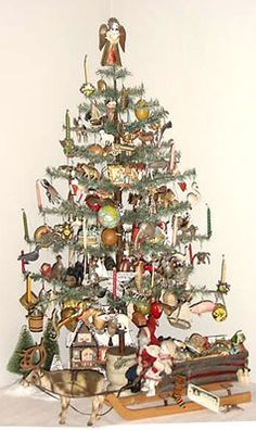 "tall antique feather tree decorated with German ""Dresden"" ornaments. The tree has built-in candle holders and has an early round wooden base. The ornaments are all embossed cardboard dating 1870 thru Antique Christmas Ornaments, Christmas Past, Victorian Christmas, Primitive Christmas, Christmas Tree Decorations, Christmas Holidays, Xmas Trees, German Christmas, Wood Ornaments"