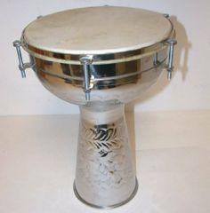 """12"""" Metal Middle Eastern Darbuka or DOUMBECK, Embossed Floral Design, 12"""" Head, 18 1/2"""" Tall, Goat Skin, Nickel Plated by DMT. $139.00. This is Middle Eastern Darbuka or called Doumbek head size 12"""" by 18"""" High fitted with selected quality Goat skin head, with bolt tunning."""