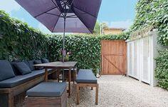 """A casa de vila não tinha quintal. Como a moradora queria um jardim, abriu mão da garagem e chamou a paisagista Michelle Simoncello Boccalato. """"Criei um painel treliçado de madeira, que fecha o espaço e serve de tutor para a tumbérgia escalar"""", conta"""