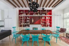 In the dining room we designed a table where the two long slabs of walnut are joined by a series of butterfly joints  lacquered in various shades of turquoise  The chairs surrounding the table are vintage Paul McCobb  lacquered in turquoise as well  The bookshelf wall is painted in a bold geometric pattern of four shades of red      Photo Credit  Andrew Cammarano #diningdesign