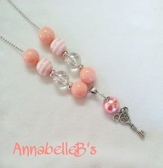 """Peach acrylic 20mm beads, silver large hole spacers, minnie key pendant and ball chain.    Necklace is 28"""" 