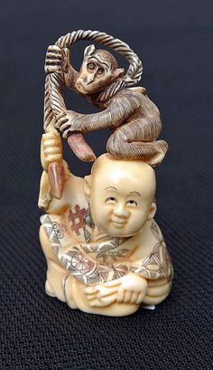 A well-executed carved and polychrome ivory netsuke featuring a boy with a monkey, Japan 19th century.