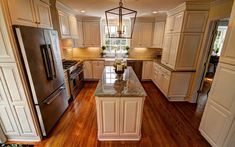We created this beautiful kitchen for our clients with warm wood floors, white cabinets, gray flecked granite countertops, stainless steel appliances and high end lighting. www.jamesriverconstruction.com