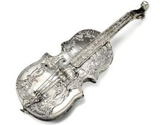 Antique Musical Instrument Silver Perfume Bottle Circa 1880. With hollow construction the bottle is in the shape of a violin (or bass violin) replete with sensuous curves of the body, four requisite strings and tuning pegs and C-curve scroll. At the bottom of the tailpiece is a silver cap with a pull cork. Superb repoussé work ornament the entire piece with a variety of intricate scenes and images.