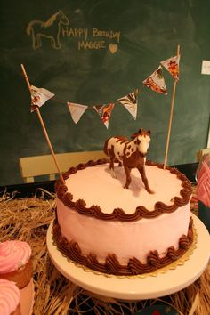 """Love the natural raffia to look like """"hay"""", pink and brown colors & the bunting and horse cake toppers"""
