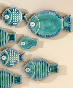 Blue Fish Plate - Chipper dots worked in porcelain over the aqua-colored glaze of the Blue Fish Plate contribute contrast and pattern like that of a genuine aquarist's prize, tempering a tropical aesthetic with fresh, cool colors and contributing a generous dash of whimsy to your wall or tabletop. The rounded body and perky tail that govern the dish's outline have a strong, iconic shape.