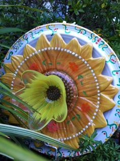Garden totem made of a dinner plate, two salad plates, and a votive holder.