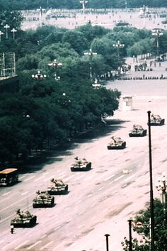 Tiananamin Square, protester squares off with tanks. Wider shot by Stuart Franklin showing the rest of the tank column.