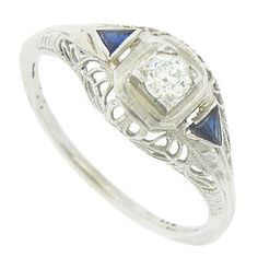 This phenomonal antique engagement ring is set with a sparkling .20 carat, H color, Si2 clarity diamond. The dazzling stone is framed by trillium cut sapphires. Abstract organic filigree frosted in delicate milgrain adorns the sides of the ring. The Art Deco ring is crafted of 18K white gold and measures 8.19 mm in width. Circa: 1920. Size 6 1/2. We can re-size.