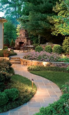 Outdoor fireplace, tiered landscaping, and curved path. Love it! The raw Copper path lights that will patina over time will look great and unique for years to come. Having the low voltage landscape lighting make this picturesque day and night.