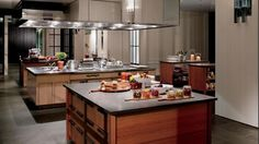 Open space kitchen with large surfaces and warm wood.