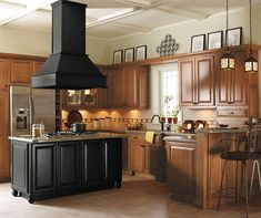 Timeless light oak cabinets pair with a beautiful black kitchen island and range hood for a look that is striking, yet surprisingly welcoming to all. Adding decorative feet creates a furniture feel, while the raised peninsula keeps visitors close at hand, ensuring that they don't get underfoot.