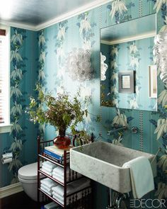 It takes a lot of guts to go big with the wallpaper, but in Katie Ridder's family's townhouse, the antique paper makes a statement as big as its pattern. The sink is custom-made, and flanked by sconces by Liza Sherman Antiques.