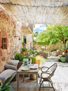 Casa de Campo con estilo.........Descansar, leer meditar... Bajo el tejado de cañizo del patio se ha dispuesto una mesita y un banco que había en la casa y se tomó como modelo para reproducir otros dos. Junto a las macetas de flores y aromáticas, este espacio invita al relax.