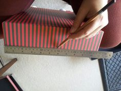 STEP 1: Rule along the short sides of your box and mark the halfway point. This is where you will cut the first hole. I decided to make my holes the width of three stripes.