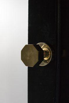 Contemporary Modern Details: Gold doorknob on a black wooden door..