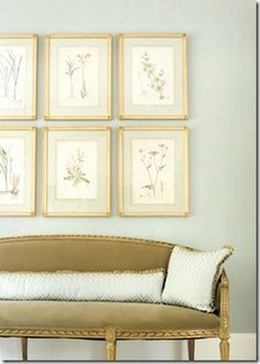 an olive green settee is used with robin egg blue pillows and walls...the prints seem to provide...contrast and relief to the blue and green.