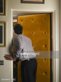 Stock Photo : Businessman looking through open doorway with studded door, rear view