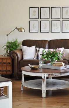 love this leather couch mixed with all the amazing linens. The gallery wall is fabulous & that round coffee table.