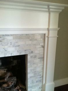 Ok this is too expensive, but like this?  Fireplace mantle and surround - hand cut, custom pattern tile (Calcutta gold marble)