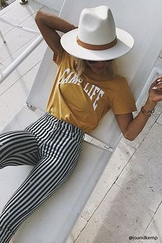 striped pants with a graphic tee and a hat