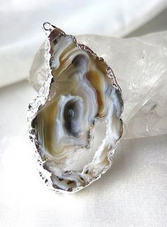 This large, natural, freeform pendant is cut from a geode slice, and reveals an awesome white crystal matrix surrounded by swirling agate in