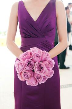 A bridesmaid wears a gorgeous purple bridesmaids dress and carries a bouquet of soft pink roses.