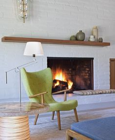 The fireplace is built into the home's 12-inch thick adobe walls and creates a snug sitting area in the living room, finished off with Eames style furnishings and minimalist accessories.    © Art Gray Photography