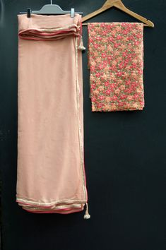 A stunning pure georgette nudesari with pink undertones and gold border with bright pink piping. The blouse piece is net with beautiful heavy floral thread work in orange and pink with a gold outline. Sari comes with a matching satin petticoat.