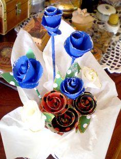 ....flores de cartulina con motivos coloridos, le agregué escarcha plateada o dorada, y las dispuse en un contenedor de un recipiente reutilizado de conserva de alimentos metálico forrado y adornado con papel mantequilla....las flores azules son de papel crepé.