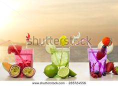 vacations and idleness concept with fruits cocktail against sunset seascape - stock photo
