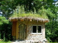 Hobbit House in the summer    One of the Hobbit houses at Wintergreen Studios. Living roof and cordwood stackwall construction. Contains a double bed, a stove, and a table for two.