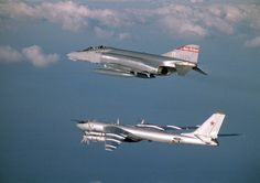 A U.S. Air Force F-4D Phantom aircraft (top) assigned to the 119th Fighter Wing ÒHappy HooligansÓ, North Dakota Air National Guard, intercepts a United Soviet Socialists Republic (Russian) TU-95 Bear bomber aircraft over the Arctic Ocean, during a flight to Keflavik, Iceland in 1983. Eight Russian TU-95 Bear bombers were intercepted by Hooligan pilots during the deployment. (A3604) (U.S. Air Force Photo) (Released)