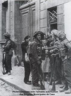 Caen, Rue Caponière, 9 juillet 1944 à 13h30. Des Caennais fêtent l'arrivée des canadiens. On trinque tandis qu'un soldat surveille aux alentours. Au centre Mme David. Il s'agit très certainement de Glens (The Stormont, Dundas and Glengary Higlanders de la 9th Brigade de la 3rd Canadian IDivision). Témoignage de Mme David: au moment de la photo, un canadien installait une ligne téléphonique en face de la maison, quelques minutes plus tard un obus le pulvérisa; ces canadiens étaient…