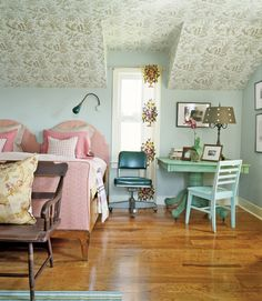 Soothing colors take over the master bedroom. Drummond added toile wallpaper on the ceiling, not the walls, and a vinyl-covered office chair lives in perfect harmony with an antique bench.   - CountryLiving.com