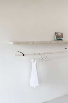 Interesting combination of rack and display shelf. Browse through clothing and discover a story of treasures on the shelf. Could also house bags, candle displays, hats....