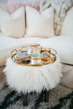 haute off the rack, home decor, world market home decor, cozy living room ideas, fall interior accessories, faux fur stool, faux fur pillow, faux fur blanket, white couch, gold mirrored tray