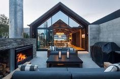 1. This sheltered outdoor living area at the Wanaka house features low sofas grouped around a large, wood-burning fireplace. The fully glazed gable ends on the main living pavilion allow a view through the house to the lake beyond.