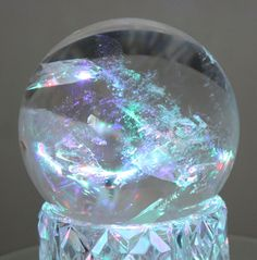 Crystal sphere with Rainbow. This is a very rare crystal with rainbow colours inside. I love how the sphere has a smooth texture, then you look inside and the rainbow colours seem to stand out.