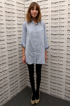 Alexa Chung in a shirtdress, black tights, and gold shoes.