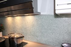 Essis kitchen wall panels, which glitter beautifully in light, are hand-crafted from recycled crushed glass with measurements ordered by the client. Kitchen Wall Panels, Crushed Glass, Recycled Glass, Backsplash, Tile Floor, Recycling, Smooth, Glitter, Face