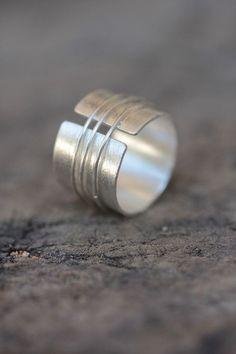 Dies ist eine handgemachte 95 % Silber Ring. Wir 0,8 mm dickem silbernen Streifen verwendet, um die Basis des Zylinders zu machen, die auch mit dem so genannten strukturiert ist Katze Fell Radierung Muster auf der Oberfläche, geben dem Artefakt seine typische handgemachte fühlen, dass Caraterizes die meisten unserer Artikel. Drei dünnen Silberdraht Schleifen werden auf der Basis des Rings um den endgültigen Entwurf fertig gelötet. Wir gestempelt unser Logo Stories auf der Innenseite des…