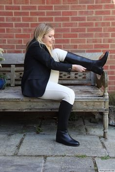 Girl in white breeches putting on riding boots