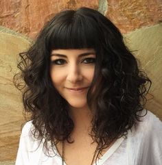 medium curly hairstyle with short blunt bangs