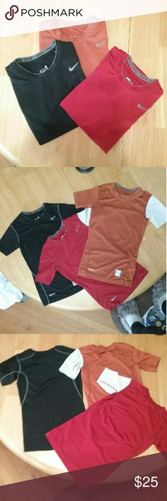 3 Boys Nike Pro T-Shirts 3 Nike Pro boys t-shirts.  1 Nike Fit Dry.  Black with gray stiching and lettering.  1 Nike Pro compression. Orange with one white sleeve and gray stiching and lettering.  1 Nike Pro tight. Red with one white sleeve and gray lettering.  84% polyester 16% spandex. Excellent condition! Nike Shirts & Tops Tees - Short Sleeve